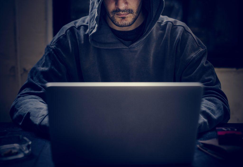 Hacker in hoodie sitting at computer