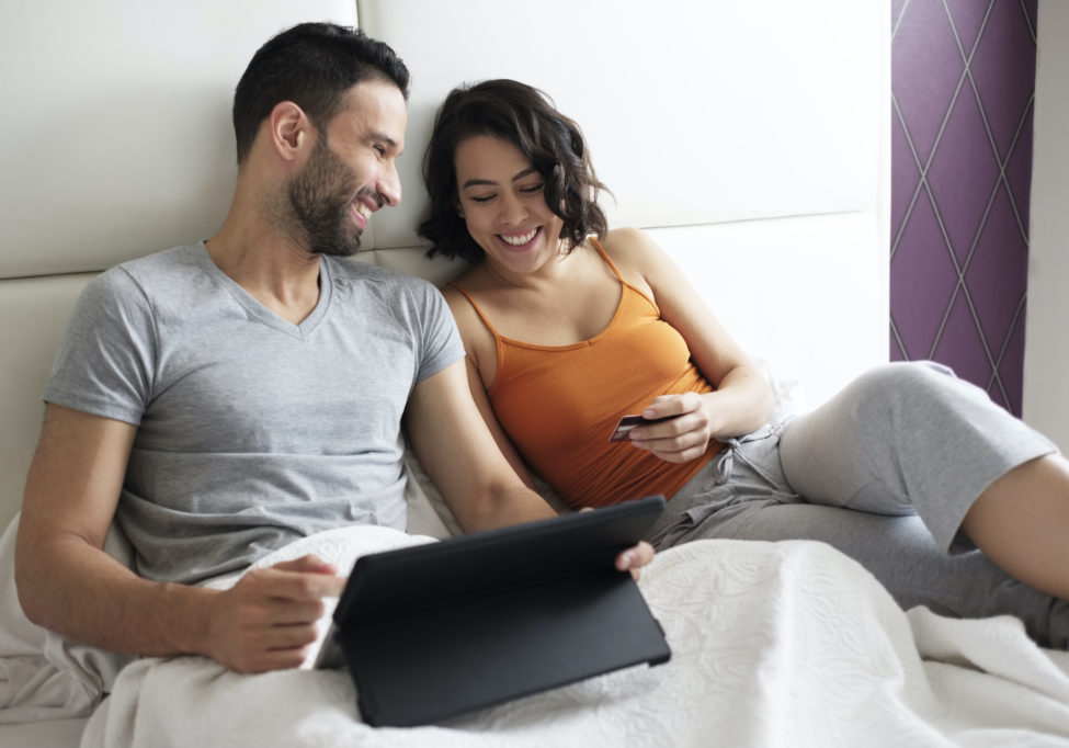 Happy man and woman using laptop computer to book travel on line. Young hispanic couple using tablet and credit card for e-commerce and online purchase